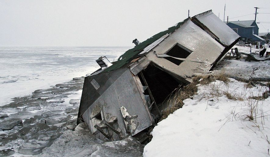FILE - In this Dec. 8, 2006, file photo, Nathan Weyiouanna's abandoned house at the west end of Shishmaref, Alaska, sits on the beach after sliding off during a fall storm in 2005. Like some other Alaska villages, the Inupiat Eskimo community of 600 is facing an expensive relocation because of erosion, which is eating away at the current site on a narrow island just north of the Bering Strait. The community will hold a special election Aug. 16, 2016, asking residents if they should develop a new community at a nearby location or stay put with added protections. (AP Photo/Diana Haecker, File)