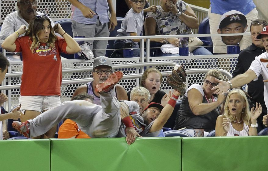 St. Louis Cardinals second baseman Kolten Wong hangs onto a foul ball hit by Miami Marlins' Martin Prado during the eighth inning of a baseball game, Friday, July 29, 2016, in Miami. (AP Photo/Lynne Sladky)
