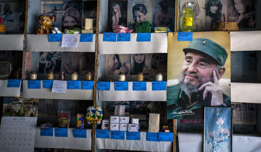 """In this July 23, 2016 photo, a picture of Cuban Revolution leader Fidel Castro is placed on the shelves of a state rationing store or """"bodega,"""" ahead of his upcoming 90th birthday in Havana, Cuba. During 47 years in power, Fidel was a constant presence for Cubans but prohibited the statues, portraits and other tributes beloved by other total leaders. (AP Photo/Desmond Boylan)"""