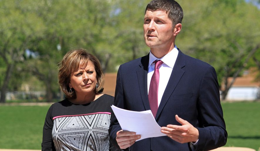 FILE - In this April 30, 2015, file photo, New Mexico Environment Secretary Ryan Flynn, right, announces a $73 million settlement between the state and the U.S. Department of Energy while flanked by New Mexico Gov. Susana Martinez during a news conference in Albuquerque N.M. The department confirmed Friday, July 29, 2016, that Flynn is resigning Aug. 15. Martinez appointed Flynn in 2013 to lead the state's environment department after a retirement forced her to reshuffle her cabinet. (AP Photo/Susan Montoya Bryan, File)