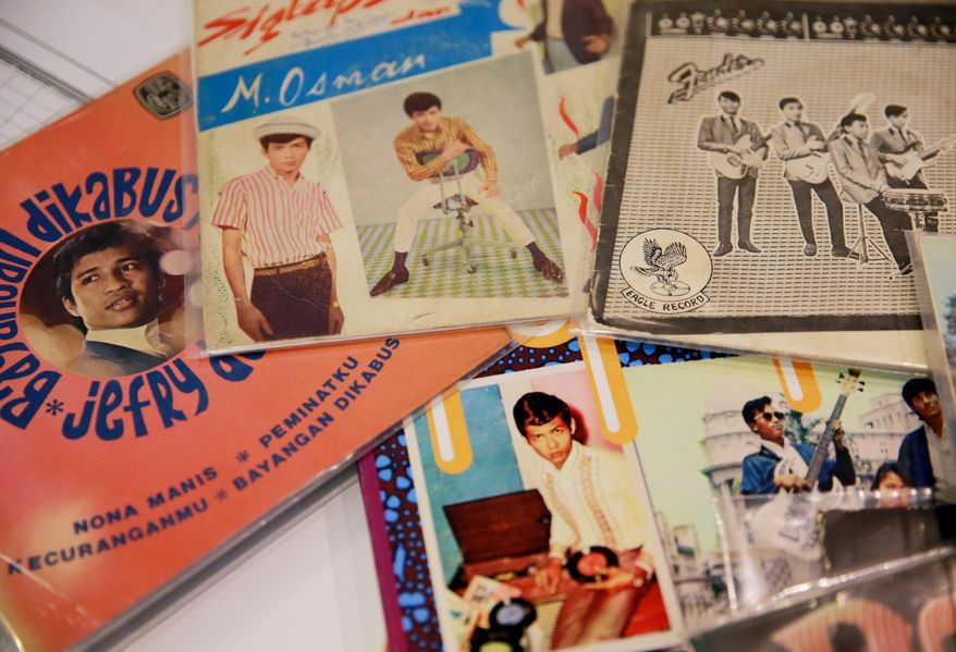 ADVANCE FOR SUNDAY, JULY 31, 2016- In this July 17, 2016 photo, some of DJ Carl Hamm's collection of Pop Yeh Yeh music are displayed in Richmond, Va. (Daniel Sangjib Min/Richmond Times-Dispatch via AP)