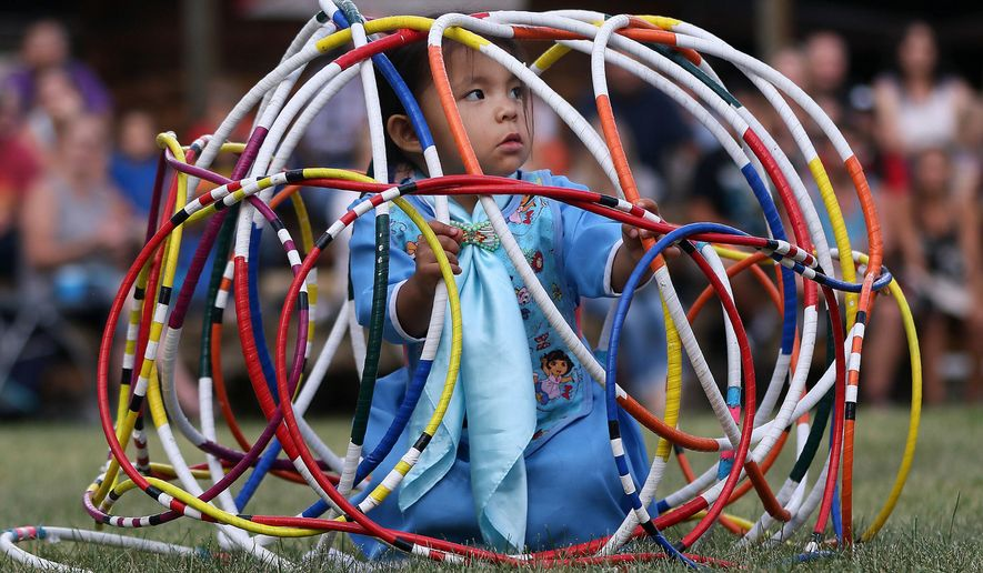 """In this Saturday, July 23, 2016 photo, Aloysia Bell, 2, sits inside a """"cage"""" of hoops as her mother finishes a hoop dance at the Indian Village at Frontier Park in Cheyenne, Wyo. The Indian Village adds to the Western story. The Wyoming Tribune Eagle reports that Sandi Iron Cloud's son said to her recently, """"When you have cowboys, you have to have Indians, too."""" And Cheyenne Frontier Days organizers realized that after holding the very first event back in 1897. (Blaine McCartney/The Wyoming Tribune Eagle via AP)"""