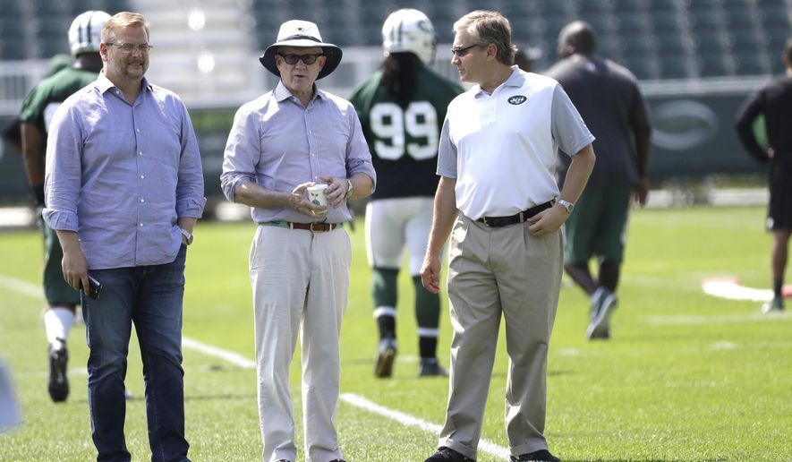 FILE - In this July 28, 2016, file photo, New York Jets owner Woody Johnson, center, stands with general manager Mike Maccagnan, left, and team president Neil Glat during NFL football training camp in Florham Park, N.J. Maccagnan allowed himself to celebrate for a moment once he knew that Ryan Fitzpatrick was coming back to the New York Jets. The two sides ended a months-long contract stalemate by agreeing to terms on a one-year, $12 million deal on Wednesday, July 27, 2016. (AP Photo/Julio Cortez, File)