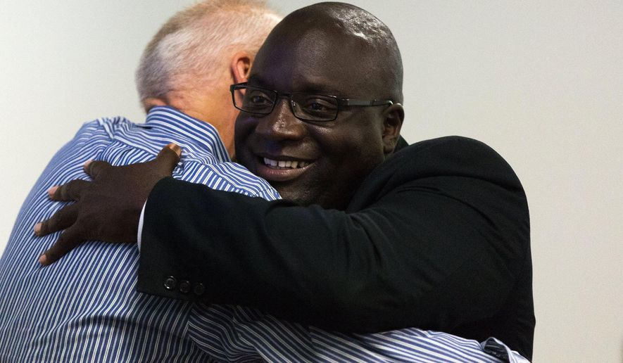 Kalamazoo City Commissioner David Anderson, left, embraces Kalamazoo City Mayor Bobby Hopewell during a Kalamazoo City Commission meeting at Kalamazoo Metro Transit in Kalamazoo, Mich. on Thursday, July 28, 2016. The meeting was held to talk about revenue options for the city of Kalamazoo. (Bryan Bennett/Kalamazoo Gazette-MLive Media Group via AP)