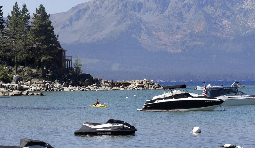 A kayaker paddles along Zephyr Cove, the sight of the 19th Annual Lake Tahoe Summit in south Lake Tahoe, Nev., in this Aug. 24, 2015, file photo. (AP Photo/Rich Pedroncelli, File)