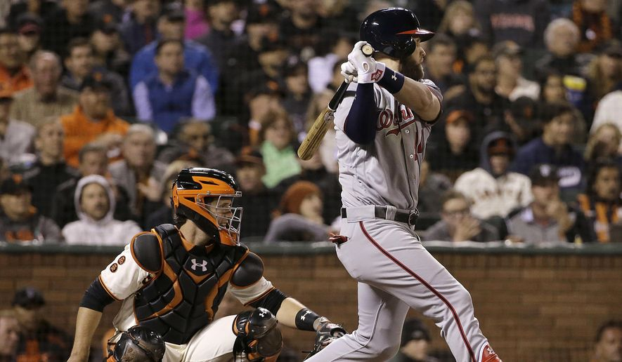 Washington Nationals' Bryce Harper, right, follows through on an RBI double in front of San Francisco Giants catcher Buster Posey during the sixth inning of a baseball game in San Francisco, Thursday, July 28, 2016. (AP Photo/Jeff Chiu)