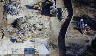 In this Oct. 28, 2013, aerial file photo, workers use backhoes to remove rubble during the demolition of Sandy Hook Elementary School in Newtown, Conn., where gunman Adam Lanza killed 20 children and six adult educators on Dec. 14, 2012. An open house for the new school, erected on the same site, is set for Friday, July 29, 2016. (AP Photo/Jessica Hill, File)