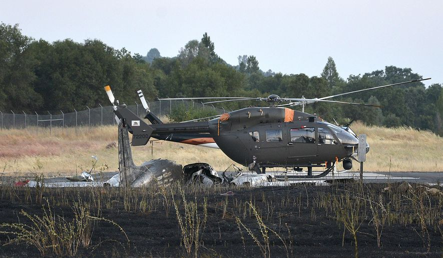 This Wednesday, July 27, 2016, photo shows a helicopter behind a small plane that crashed at the Columbia Airport in Columbia, Calif. A Northern California family of four was killed after the plane crashed and burned as it tried to land on a runway Wednesday. (Erin Tracy/The Modesto Bee via AP)