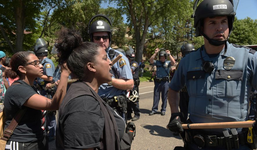 FILE - In this Tuesday, July 26, 2016 file photo, Wintana Melekin speaks to a line of St. Paul police as police and protesters face off on Summit Avenue, a block from the Governor's residence, in St. Paul, Minn. The images offer a sharp contrast: In some places, police in SWAT gear wield batons or carry long guns as they corral streets teeming with protesters. Elsewhere, officers are seen riding around on bicycles, mingling with demonstrators and even posing for selfies. (Scott Takushi/Pioneer Press via AP, File)