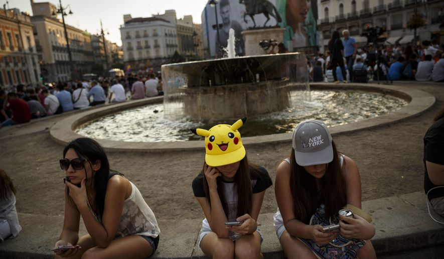 Spanish fans play the highly addictive Pokemon Go game during a gathering in central Madrid, Spain, Thursday, July 28, 2016, to play the computer game.  In the game players try to capture, battle, and train virtual creatures in their real world locations using the GPS and camera on their smart devices. (AP Photo/Daniel Ochoa de Olza)