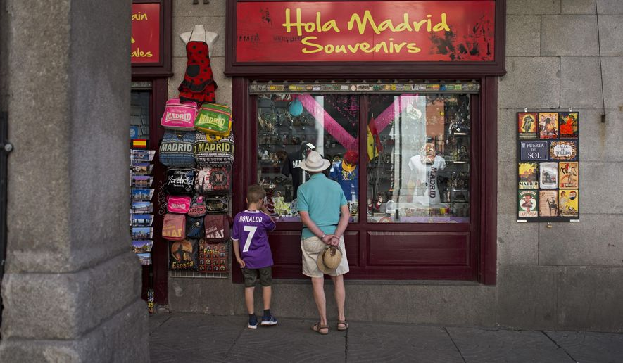 People look at the display window of a Spanish souvenirs shop in downtown Madrid, Spain, Friday, July 29, 2016. Spain's acting Prime Minister Mariano Rajoy was to begin calling opposition party leaders Friday in a bid to get badly needed parliamentary support after accepting the king's petition to try to form a government following last month's inconclusive elections. (AP Photo/Francisco Seco)