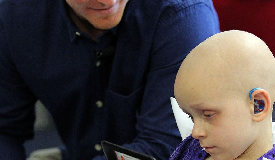 FILE - In this March 10, 2014, file photo, patient Micah Ahern, 4, plays a with a gaming device as Cincinnati Bengals quarterback Andy Dalton, a former TCU player, watches in Fort Worth, Texas. Micah, who battled cancer and was part of TCU's baseball team for three consecutive trips to the College World Series. died Thursday, July 28, 2016.(Ron Jenkins/Fort Worth Star-Telegram via AP)