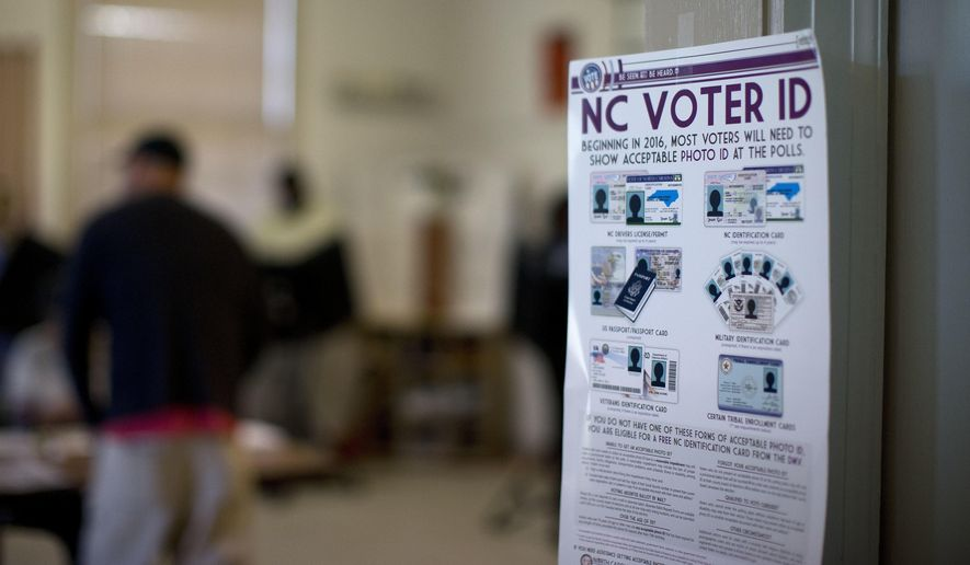 This photo taken March 15, 2016, shows a NC Voter ID rules posted at the door of the voting station at the Alamance Fire Station in Greensboro, N.C. (Andrew Krech/News & Record via AP)