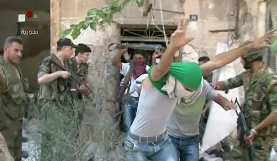 This still image from Syrian state TV video shows young men with their faces covered surrendering to government forces in Aleppo, Syria, on July 30, 2016, Syrian state media is reporting that dozens of families have started leaving besieged rebel-held neighborhoods in the northern city of Aleppo after the government opened safe corridors for civilians and fighters who want to leave. The Russian military says 169 civilians have left through the corridors since they were set up, but Syrian opposition activists say no civilians have left besieged parts of the city. (Syrian State TV via AP)