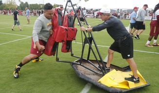 Washington Redskins guard Shawn Lauvao (77) works on the sled with offensive line coach, Bill Callahan, after the morning walk through at the Washington Redskins NFL football teams training camp in Richmond, Va., Saturday, July 30, 2016. (AP Photo/Steve Helber)