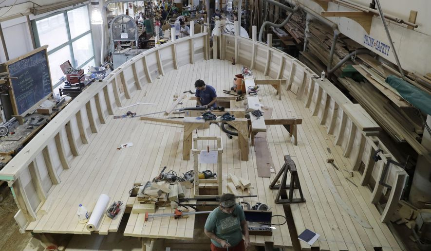 In a Wednesday, July 13, 2016 photo, Dave Dormond and India Gilham-Westerman work on a replica of a privateer ship for the Museum of the American Revolution, at the Independence Seaport Museum in Philadelphia. The Museum of the American Revolution will feature one-half of a life-sized privateer ship as a primary immersive exhibit when it opens next year, blocks from Independence Hall and the Liberty Bell. (AP Photo/Matt Rourke)