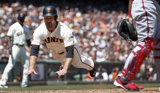San Francisco Giants' Mac Williamson, left, slides into home plate past Washington Nationals catcher Pedro Severino, right, on a ground ball by Angel Pagan during the fourth inning of a baseball game in San Francisco, Saturday, July 30, 2016. Pagan was out at first base. (AP Photo/Tony Avelar)
