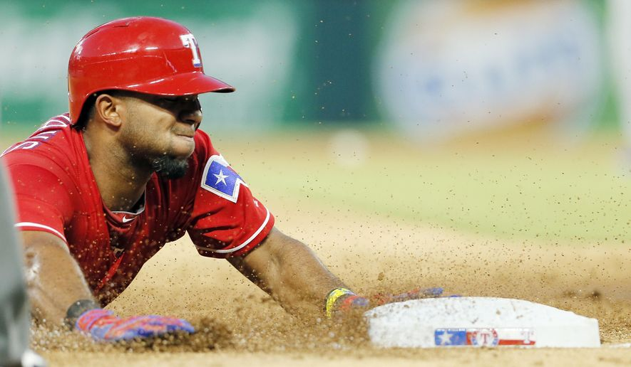 Texas Rangers' Elvis Andrus slides into third after hitting a triple during the third inning of a baseball game against the Kansas City Royals, Saturday, July 30, 2016, in Arlington, Texas. (AP Photo/Brandon Wade)