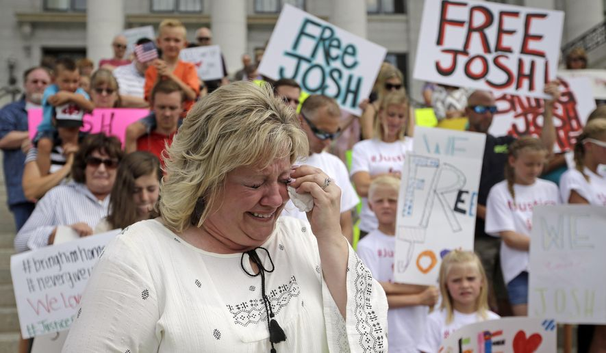 Laurie Holt, the mother of Josh Holt, an American jailed in Venezuela, cries during a rally at the Utah State Capitol Saturday, July 30, 2016, in Salt Lake City. Laurie Holt hosted the rally in hopes of drawing attention to her son's case. Laurie Holt says her son was mistakenly accused, and has lost weight and gotten sick since he was jailed nearly a month ago. Josh Holt was arrested on suspicion of weapons charges after he traveled to Venezuela on a tourist visa to marry a fellow Mormon he met on the internet. More than 100 rallied at the Utah State Capitol. (AP Photo/Rick Bowmer)