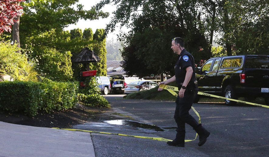 A police officer tapes off the the closest proximity to the multiple murder scene in the Chenault Beach neighborhood of Mukilteo, Wash., Saturday July 30, 2016.  A suspect was apprehended three counties away, said Officer Myron Travis of the Mukilteo Police Department. (Alan Berner/The Seattle Times via AP)