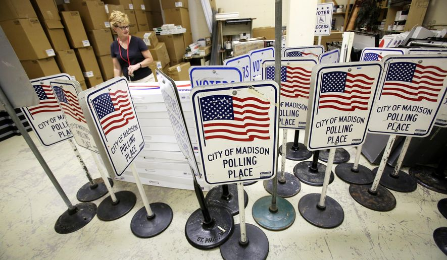 Jean Phelps, certified municipal clerk for the city of Madison, looks over polling place signs whose bases have become rusted because of flooding in the basement of the Village Mall in Madison, Wis., Friday, July 29, 2016. The signs won't be replaced, but are in storage for now.(Amber Arnold/Wisconsin State Journal via AP)