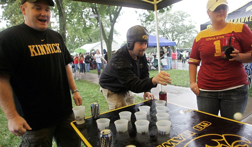 ADVANCE FOR WEEKEND EDITIONS JULY 30-31 - In this Saturday, Sept. 13, 2008 photo, Josh Beachy, of Coralville, center, bounces the ball during a game of beer pong as Lucas Kuhlmann, left, of Iowa City, and Laura Tigges, of West Des Moines, look on as they tailgate before Iowa's game against Iowa State in Iowa City. A debate is brewing over expanding beer sales at Iowa college football games. A key state lawmaker is proposing a legislative review, while Gov. Terry Branstad and some other policy makers want to let state university officials and the Iowa Board of Regents control the bar taps, Friday, July 29, 2016. (The Des Moines Register via AP)