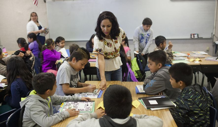 In this June 1, 2016 photo, teacher Monica Villegas, an exchange teacher from Mexico, instructs students at the Twin Falls School District's migrant summer school at Oregon Trail Elementary School in Twin Falls, Idaho. A migrant summer school helps fill education gaps while keeping children out of farm fields. (Stephen Reiss/The Times-News via AP)