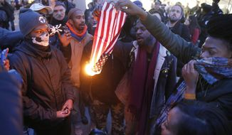 In this Feb. 23, 2016 file photo, protesters burn an American flag in Chicago. Champaign County Ill. (AP Photo/Charles Rex Arbogast, File)
