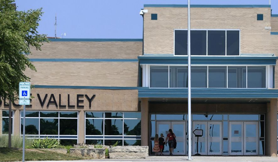 FILE - In this Monday June 20, 2016 file photo, a family approaches the front doors at Blue Valley Northwest High School in Overland Park, Kan. Blue Valley had fewer than 900 students in 1970. It is now the state's fourth-largest district, with more than 22,500 students and five high schools, the newest one opening in 2010. (AP Photo/Orlin Wagner, file)