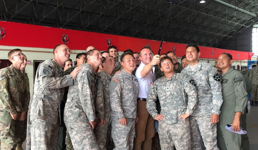 """U.S Army Secretary Eric Fanning, fourth from right, takes a selfie with fellow personnel during an annual joint military exercise with the Malaysian army in Johore Bahru, Malaysia, Saturday, July 30, 2016. Fanning says annual war games between the United States and South Korea will go ahead next month, despite North Korea's warning of a """"vicious"""" showdown if the military drills proceed. (AP Photo/Eileen Ng)"""