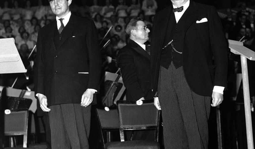 FILE - In this Nov. 23, 1944 file photo, former New Hampshire Governor and U.S. Ambassador to Britain, John Winant, left, and Britain's Prime Minister Winston Churchill stand at attention while the National Anthem is played during the Great Thanksgiving Day celebration to America at the Royal Albert Hall in London. Winant, who died at age 58, faded into obscurity until recent years, when a group formed in New Hampshire to raise money for a bronze statue of him. (AP Photo/File)