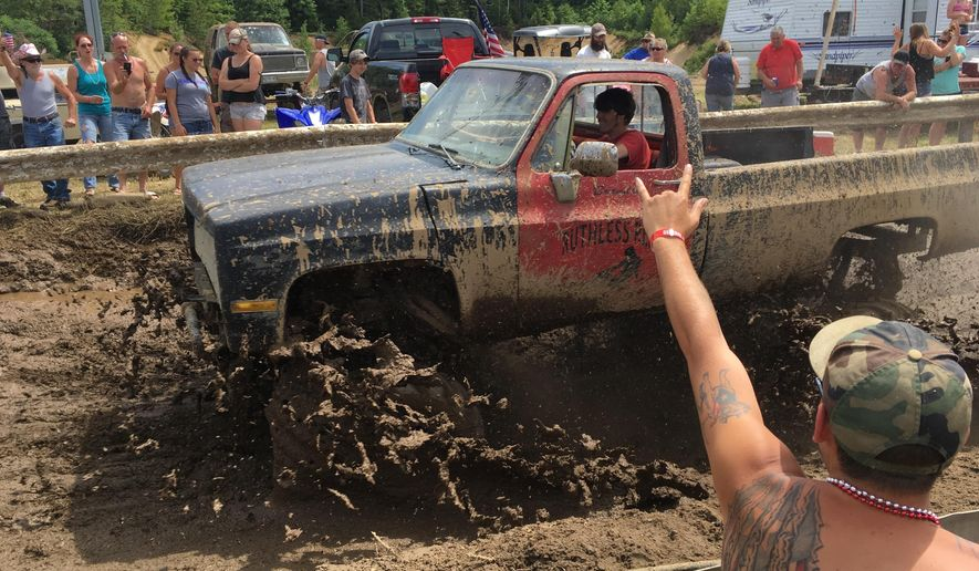 "Spectators cheer as a pickup truck splashes through mud at an event formerly called the Redneck Olympics on Saturday, July 30, 2016, in Hebron, Maine. The organizer now calls the event the ""Redneck Blank"" after Olympic officials complained about the name. (AP Photo/David Sharp)"