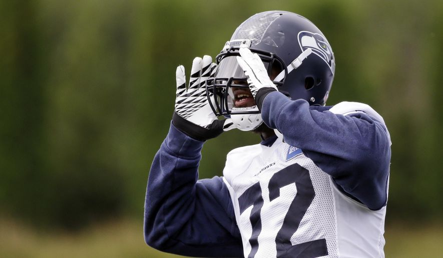 Seattle Seahawks' Michael Bennett yells to fans to start a chant during the team's NFL football training camp Saturday, July 30, 2016, in Renton, Wash. (AP Photo/Elaine Thompson)