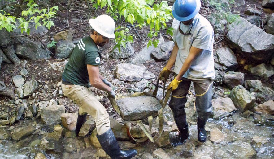 ADVANCE FOR WEEKEND EDITIONS JULY 30-31 - In this Monday, June 13, 2016, photograph, Brian Roders, left, and Adam Joret with the U.S. Forest Service carry a rock to create an embankment along the Hanging Lake trail east of Glenwood Springs, Colo. (Chelsea Self/Glenwood Springs Post Independent via AP) MANDATORY CREDIT