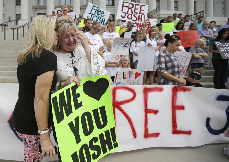 Laurie Holt, right, the mother of Josh Holt, an American jailed in Venezuela, is comforted by family friend Lori Fitch, left, as she cries during a rally at the Utah State Capitol Saturday, July 30, 2016, in Salt Lake City. Laurie Holt hosted the rally in hopes of drawing attention to her son's case. Laurie Holt says her son was mistakenly accused, and has lost weight and gotten sick since he was jailed nearly a month ago. Josh Holt was arrested on suspicion of weapons charges after he traveled to Venezuela on a tourist visa to marry a fellow Mormon he met on the internet. More than 100 rallied at the Utah State Capitol. (AP Photo/Rick Bowmer)