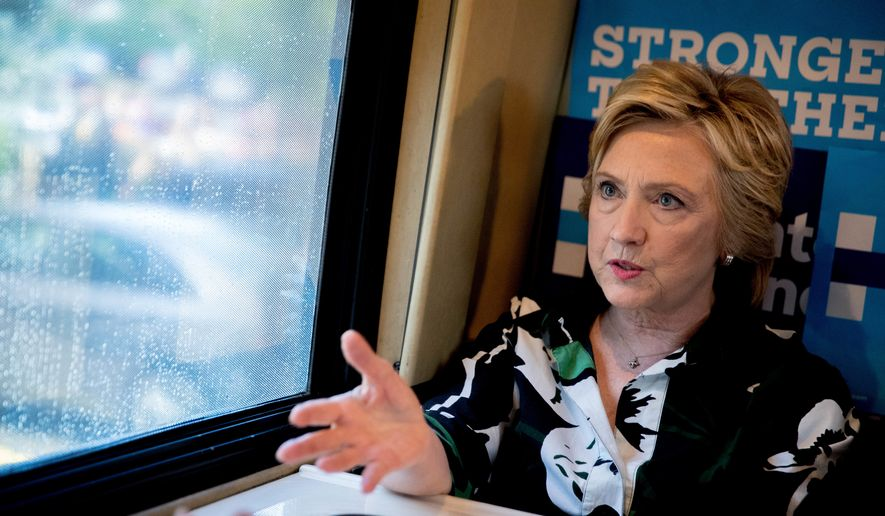 Democratic presidential candidate Hillary Clinton speaks on her campaign bus after visiting Imani Temple Ministries in Cleveland, Sunday, July 31, 2016. Clinton and running mate Sen. Tim Kaine are on a three day bus tour through the rust belt. (AP Photo/Andrew Harnik)