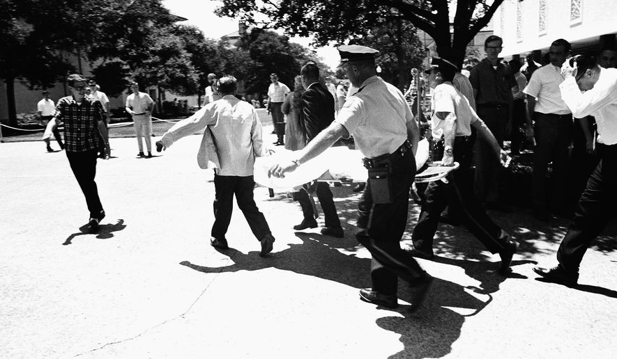 FILE - In this Aug. 1, 1966 file photo, one of the victims of Charles Joseph Whitman, the sniper who gunned down victims from a perch in the University of Texas tower, is carried across the campus to a waiting ambulance in Austin. The unidentified victim was gunned down inside the tower, according to police on the scene. Monday, Aug. 1, 2016, marks the 50th Anniversary of the mass shooting. (AP Photo, File)