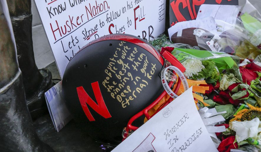 A helmet, signs and flowers are among the items Wednesday, July 27, 2016, at a makeshift memorial in Lincoln, Neb., for Nebraska college football punter Sam Foltz, who died Saturday in a Wisconsin car crash. The 22-year-old Foltz and former Michigan State punter Mike Sadler died in a single-car crash near Merton, Wis., after working at a kicking clinic. A funeral Mass is to be held for Foltz on Saturday at Blessed Sacrament Catholic Church in Grand Island, Neb. (AP Photo/Nati Harnik)