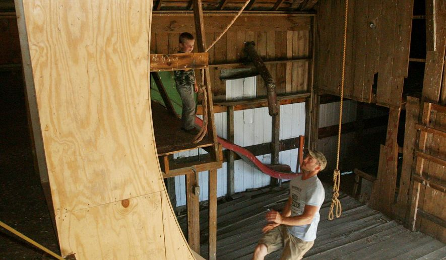 """ADVANCE FOR SUNDAY JULY 31 - In this July 14, 2016 photo, Donovan Schneider runs up his homemade version of the warped wall while training for American Ninja Warrior in his barn in Juniata, Neb. Today at 5-foot-6 and 135 pounds, the Juniata resident still isn't the type one would expect to see competing in the """"American Ninja Warrior"""". Yet that's where the 28-year-old husband and father of four wound up after his audition video tape submission in January won him a nod on the popular television show. (Amy Roh/The Hastings Tribune via AP)"""