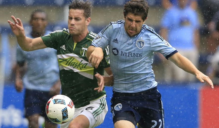 Portland Timbers forward Lucas Melano (26) and Sporting Kansas City midfielder Connor Hallisey (22) race for the ball during the first half of an MLS soccer match in Kansas City, Kan., Sunday, July 31, 2016. (AP Photo/Orlin Wagner)