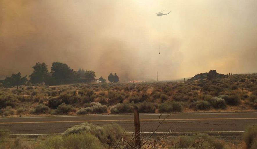 In this Saturday, July 30, 2016 photo provided by Vince O'Daye, a helicopter flies over plumes of smoke from a wildfire in the community of Sutcliffe, Nev., about 35 miles north of Reno, Nev. The wildfire was deterred Sunday from burning the tribal town that had evacuated hundreds of residents. (Courtesy of Vince O'Daye via The AP)