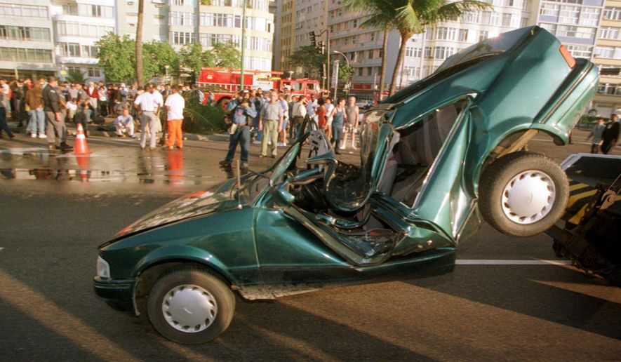 FILE - This June 28, 1999, file photo shows a smashed Ford sits upended on Avenida Atlantica along the Copacabana beach Monday, June 28, 1999 in Rio de Janeiro. Zika is in the spotlight but health experts say the most likely cause of death or serious harm to travelers everywhere is injuries from car accident, falls, crime or other mishaps.  (AP Photo/Geraldo Perez, File)