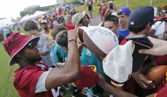 Washington Redskins cornerback Josh Norman signs autographs for fans after the morning walk through session at the NFL football teams training camp in Richmond, Va., Monday, Aug. 1, 2016. (AP Photo/Steve Helber) **FILE**