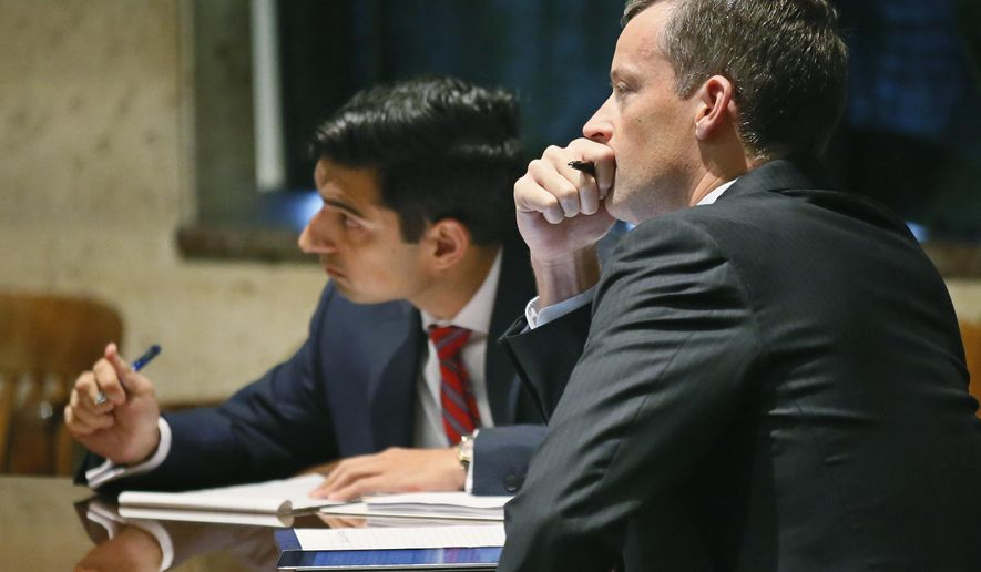 Attorneys Mithun Mansinghani, left, and Patrick Wyrick, right, of the Oklahoma office of the Attorney General, listen to arguments on a retail liquor group's request to block a November ballot measure on whether strong beer and wine can be sold in grocery stores in Oklahoma City, Monday, Aug. 1, 2016. An Oklahoma County judge denied the request. (AP Photo/Sue Ogrocki)