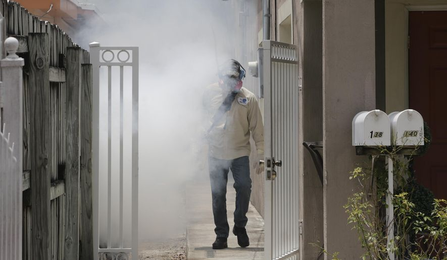 A Miami-Dade County mosquito control worker sprays around a home in the Wynwood area of Miami on Monday, Aug. 1, 2016. The CDC has issued a new advisory that says pregnant women should not travel to a Zika-stricken part of Miami, and pregnant women who live there should take steps to prevent mosquito bites and sexual spread of the virus. (AP Photo/Alan Diaz) ** FILE **