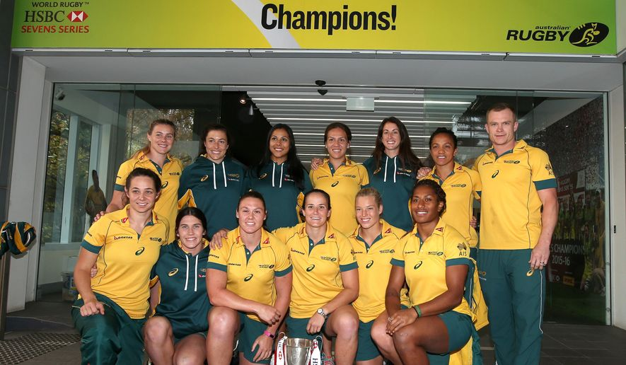 In this June 1, 2016, photo the Australian women's rugby sevens team, including Ellia Green in the front row at right, pose with their World champions trophy in Sydney. The so-called fastest woman in world rugby, for a long time Green trained in track and field and competed at international level for Australia before making a sudden move into a rough-and-tumble sport that is making its Olympic debut in Rio de Janeiro. (AP Photo/Rick Rycroft)