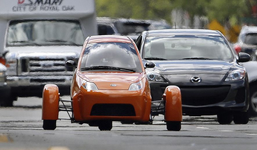 FILE - In this Aug. 14, 2014 file photo, the Elio, a three-wheeled prototype vehicle rolls in traffic in Royal Oak, Mich. In July 2016, Rhode Island joined dozens of other states enacting new rules classifying the autocycle, allowing drivers to operate one without a motorcycle license or endorsement. Autocycles have three wheels 'typically, two in the back and one in the front. They also have steering wheels, foot pedals and are sometimes enclosed. (AP Photo/Paul Sancya, File)