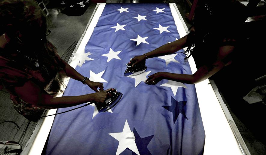 ADVANCE FOR USE WEDNESDAY, AUG. 3, 2016 AND THEREAFTER-Employees Lottie Penick, left, and Melissa Hodnett iron stars onto a United States flag at Annin Flagmakers in South Boston, Va., on Wednesday, July 6, 2016. Ask the workers at the factory to name life's most important things and family, work and faith are repeated. Presented the chance to live in a foreign land, the idea is uniformly rejected, with each saying America can't be beat. And nudged to sum up what this country's people share, they invoke their handiwork and what it stands for _ freedom, opportunity and pride. (AP Photo/Gerry Broome)