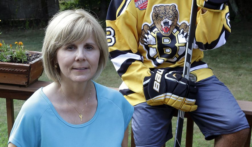 In this Friday, July 29, 2016, photo, Debbie Amorelli poses with her son, Chris, 17, at their home in Upton, Mass. Debbie and her husband spend about $10,000 a year to pay for Chris to play hockey. They are able to pay for it thanks to an inheritance from his grandfather but keep telling him that this is money that could be going toward college. (AP Photo/Elise Amendola)