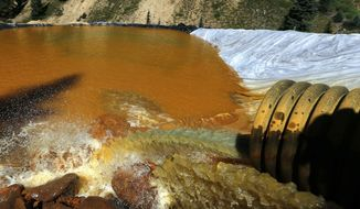 In this Aug. 14, 2015, file photo, water flows through a series of retention ponds built to contain and filter out heavy metals and chemicals from the Gold King mine chemical accident, in the spillway about a quarter mile downstream from the mine, outside Silverton, Colo. (AP Photo/Brennan Linsley, File)
